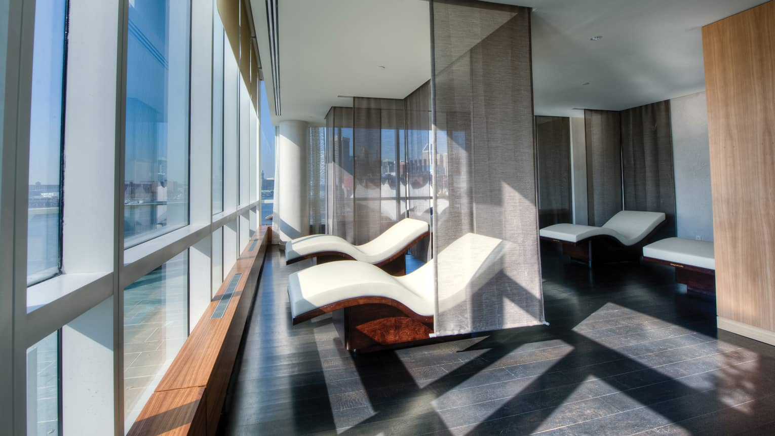 Two curved white spa chairs divided by sheer panel curtains in front of floor-to-ceiling windows