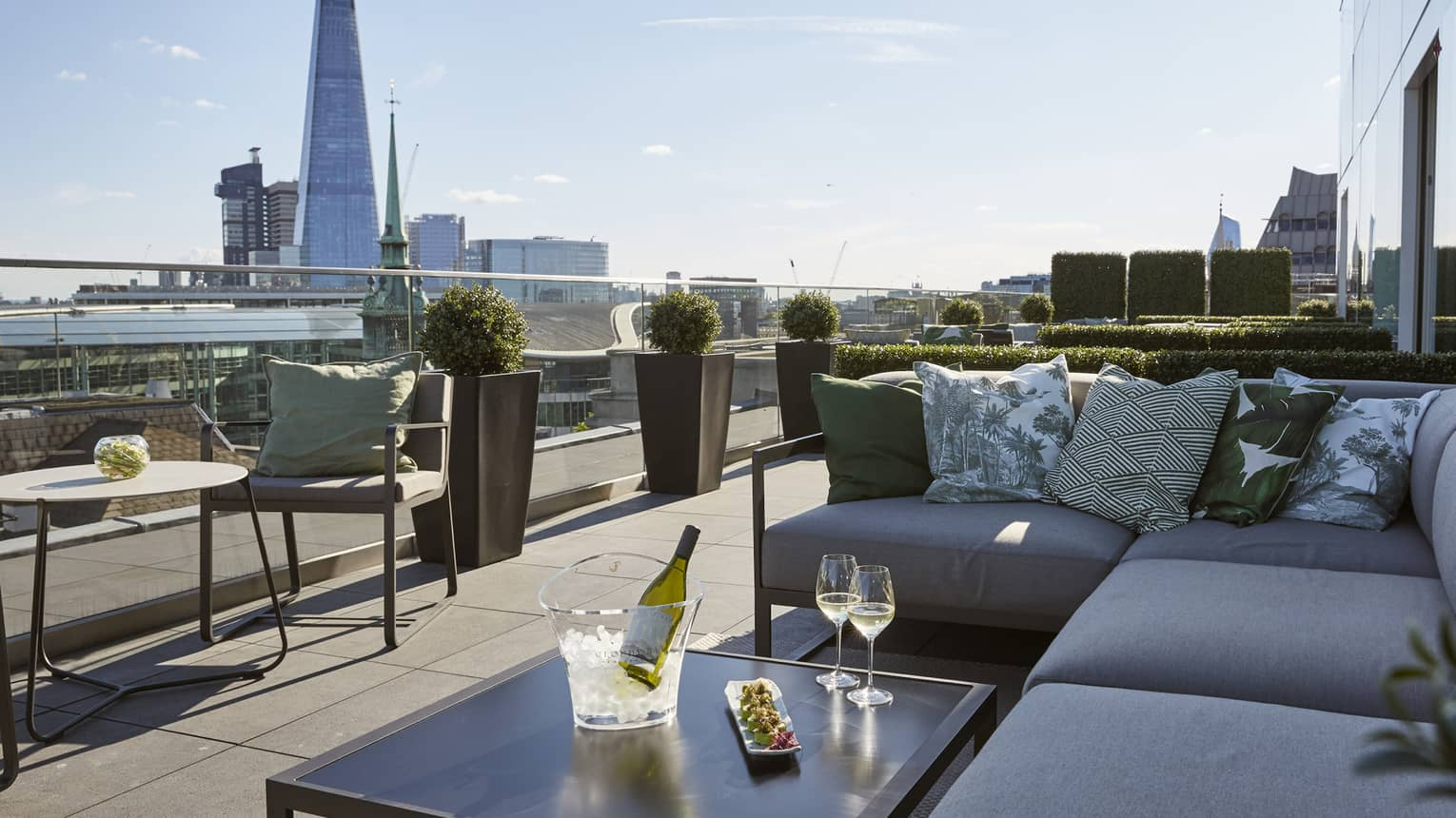 Sushi and chilled wine are arranged on an outdoor patio with a view of the London skyline