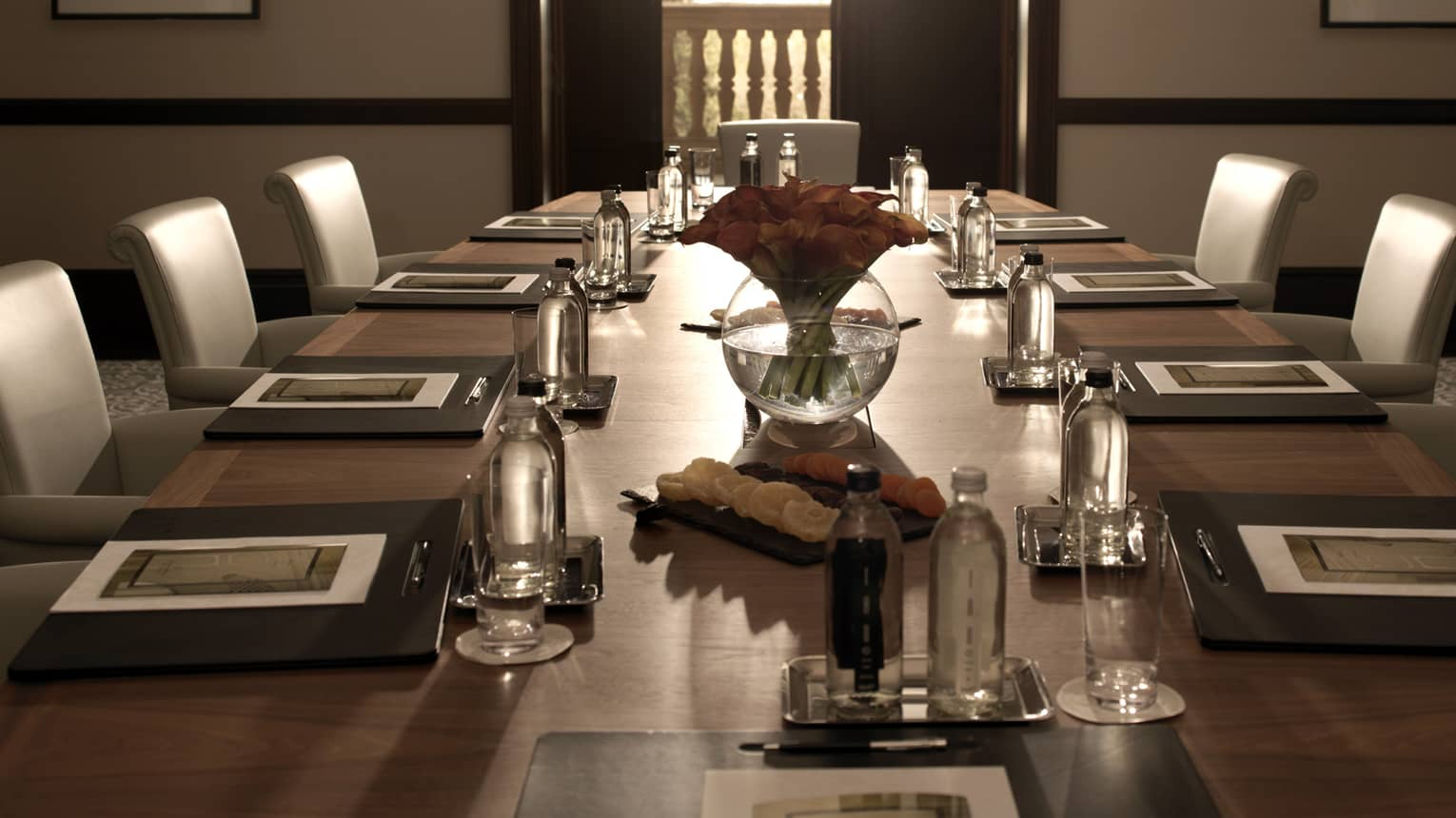 Sleek leather chairs around large, dark wood boardroom table set for business event