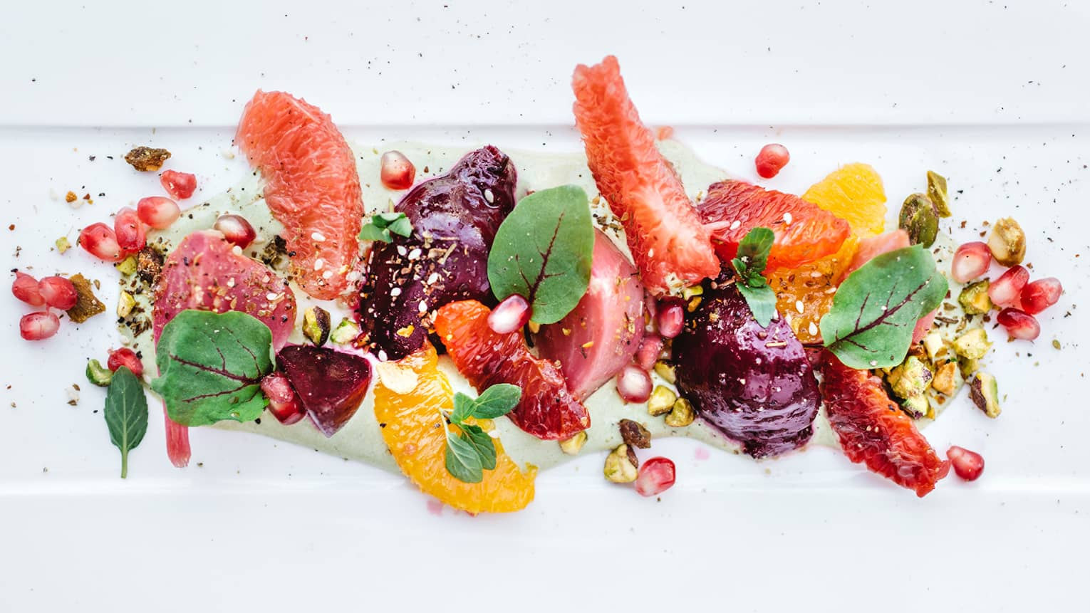Roast beet salad, grapefruit wedges, pomegranate seeds on white dish