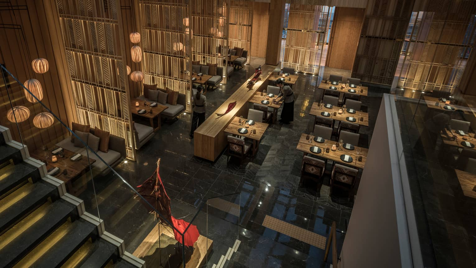 Aerial view over dark Kioku restaurant dining room, staircase