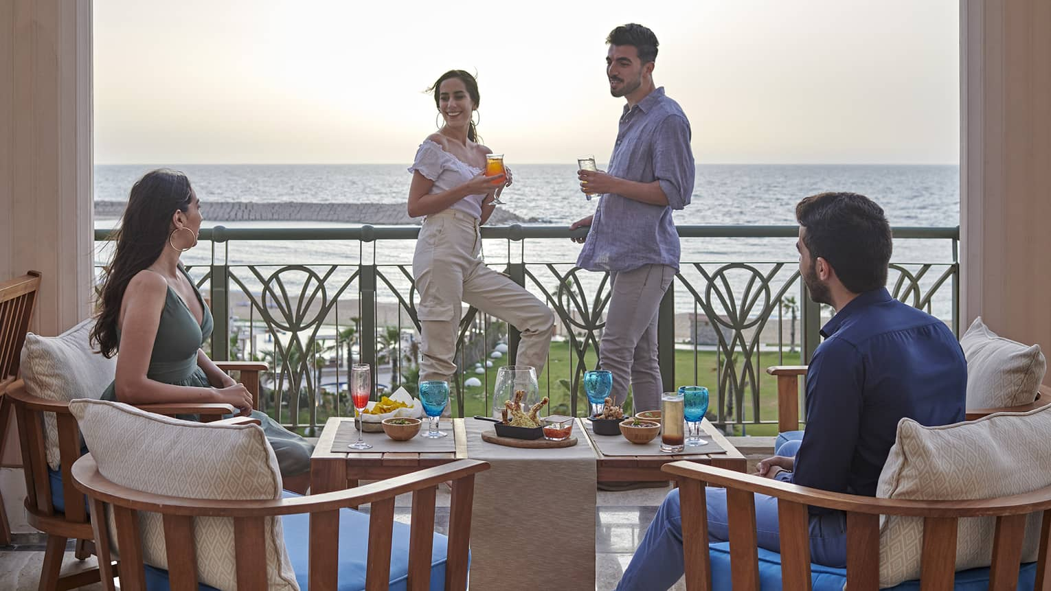 Two couples lounge on a terrace overlooking the ocean at four seasons alexandria
