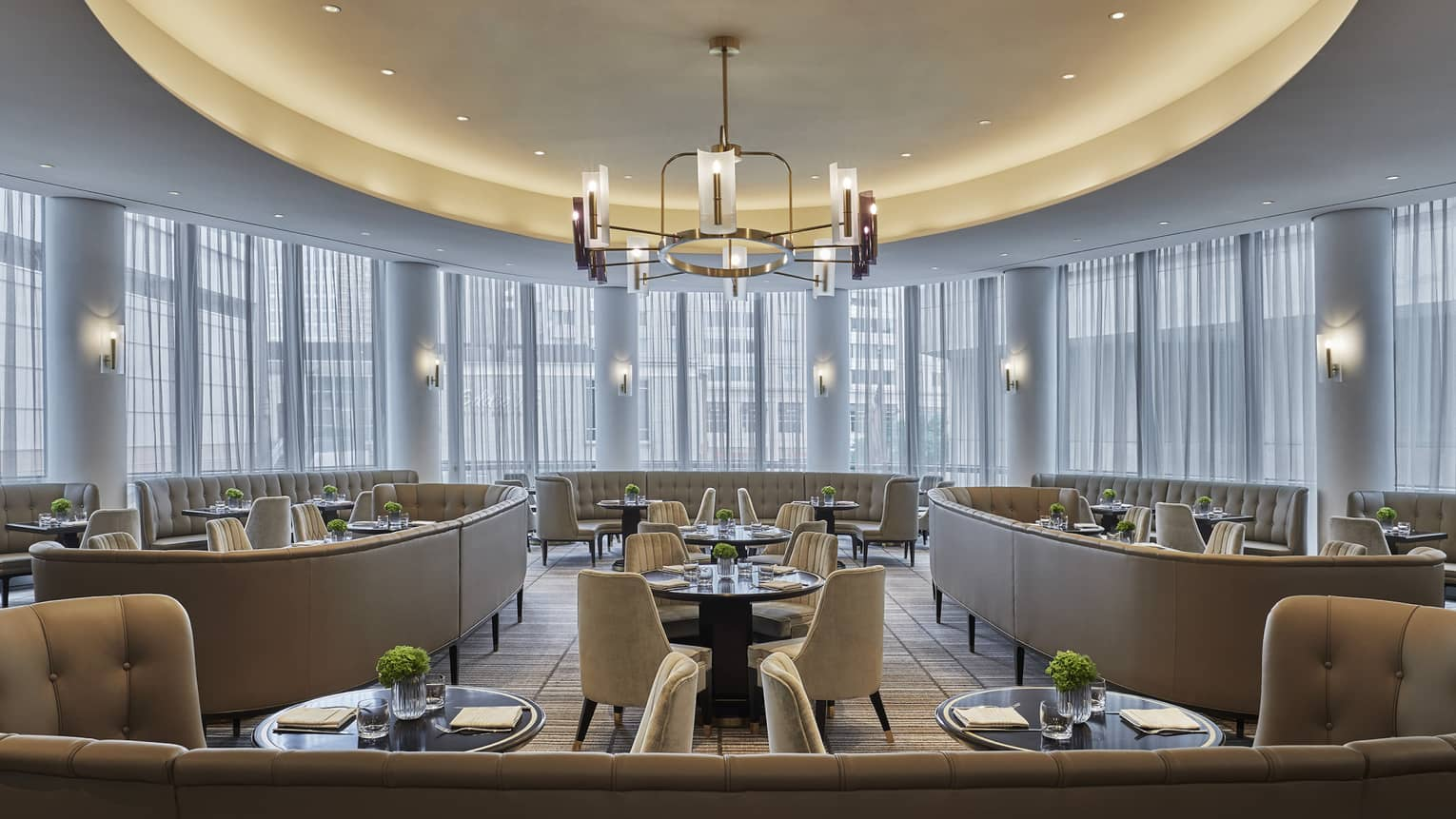 One-One restaurant is empty, but ready with guests, with tables set with menus, plates and greenery