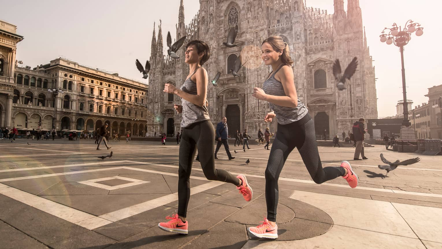 Two women wearing exercise clothes, Nike shoes, jog across outdoor courtyard by historic church
