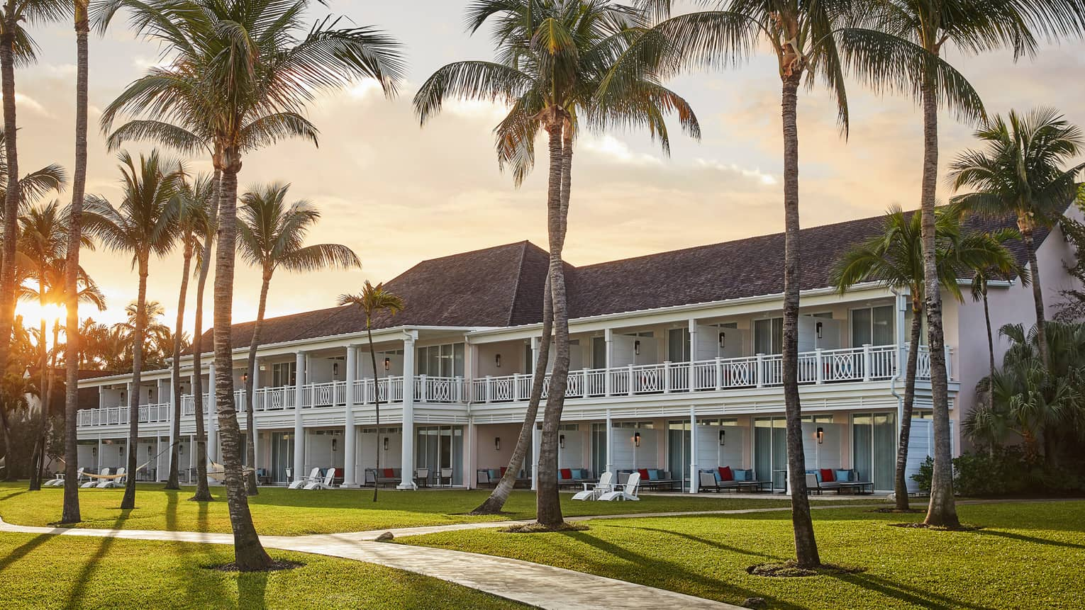 Tall palm trees, sunset over Hartford Wing two-storey white resort building with decorative balconies