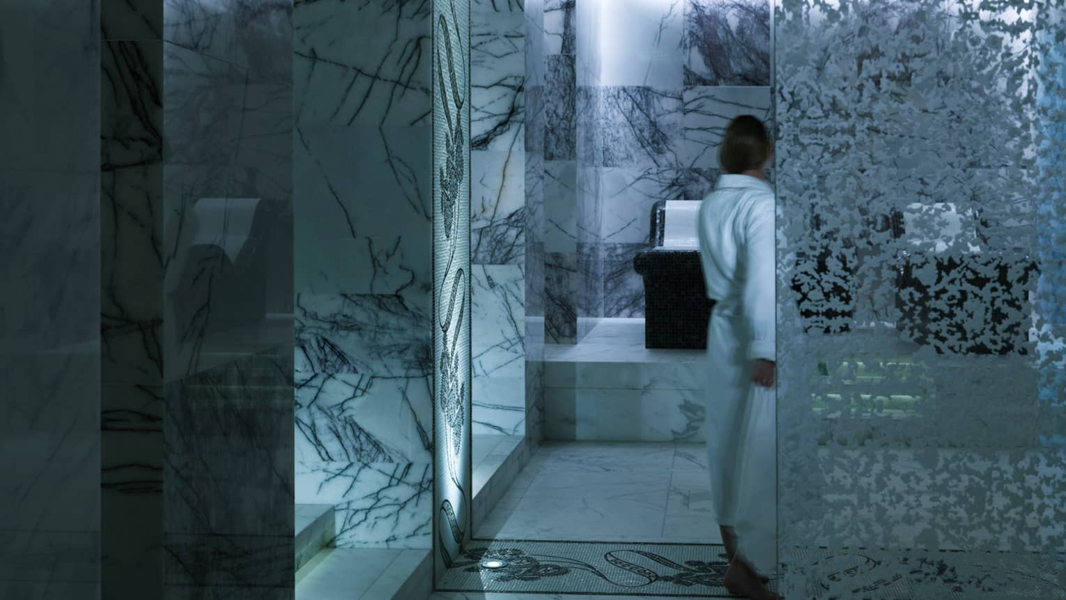 Back of woman in white bathrobe holding towel in black-and-white marble spa room