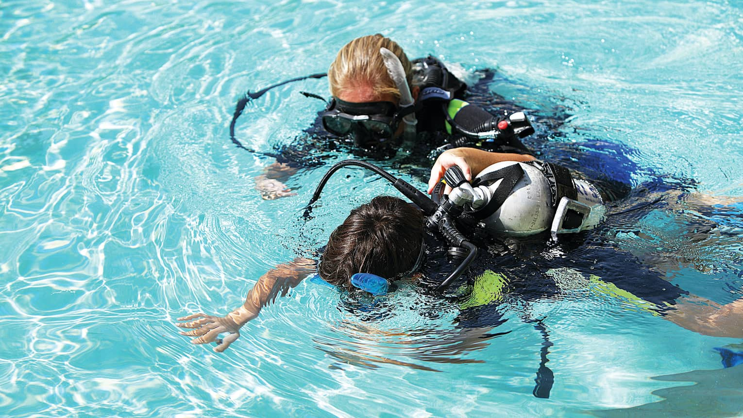 Two scuba divers look down into water