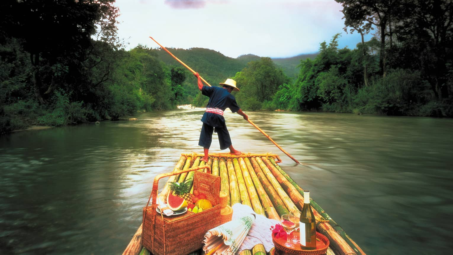 Man steers boat down Mae Tang River in front of picnic baskets, fruit and wine