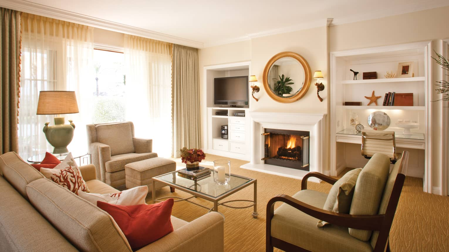 Two-bedroom resort residence living room sofa and armchairs by fireplace with white mantle, mirror, desk