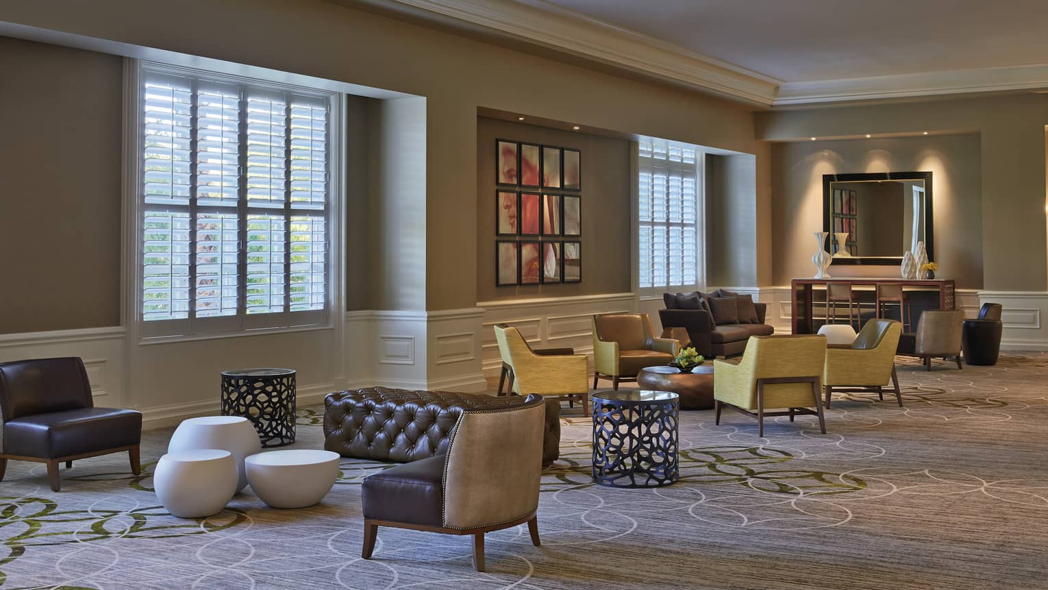 Modern armchairs, ottomans by windows in carpeted Four Seasons Ballroom Foyer