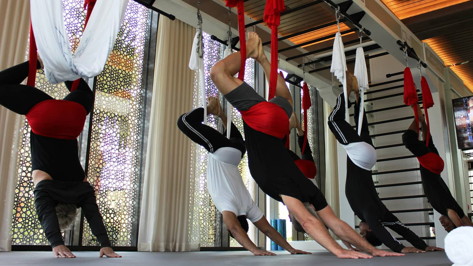 Fitness class, people hanging upside-down from red and white yoga hammocks