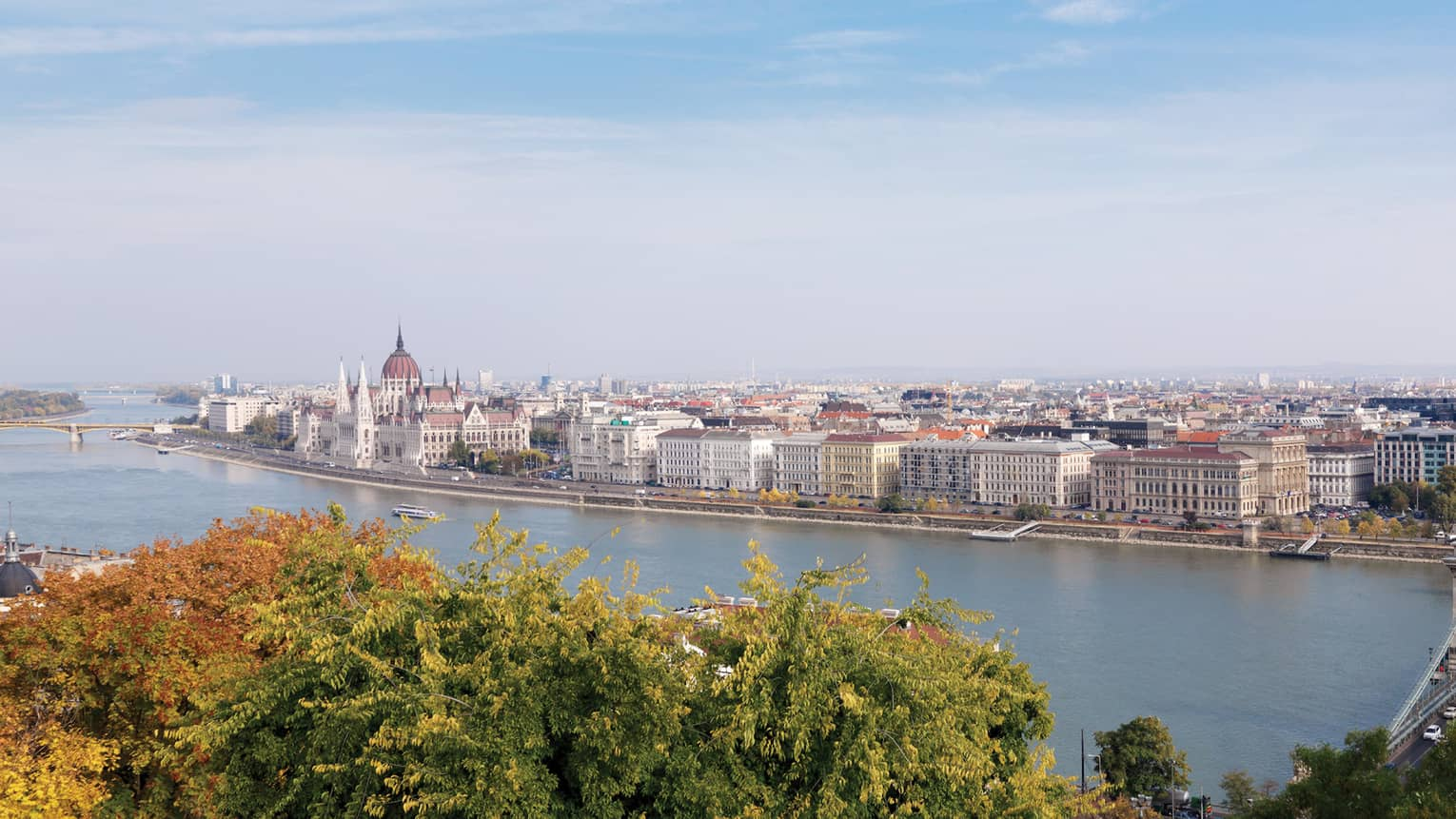 Looking down past trees at Danube river, Budapest city waterfront buildings on sunny autumn day