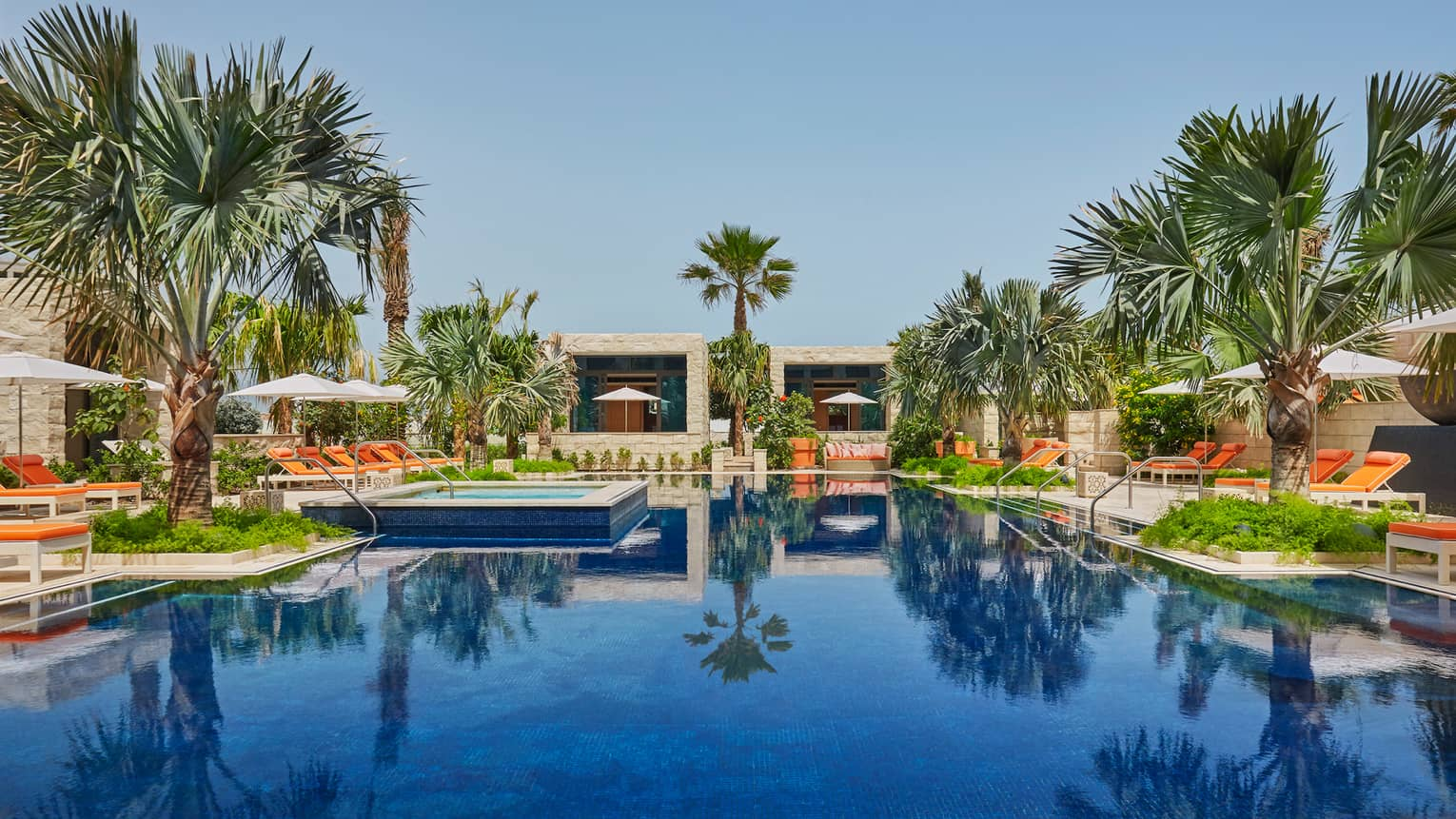 Azure adults-only swimming pool, surrounded by palm trees, orange lounge chairs, cabanas
