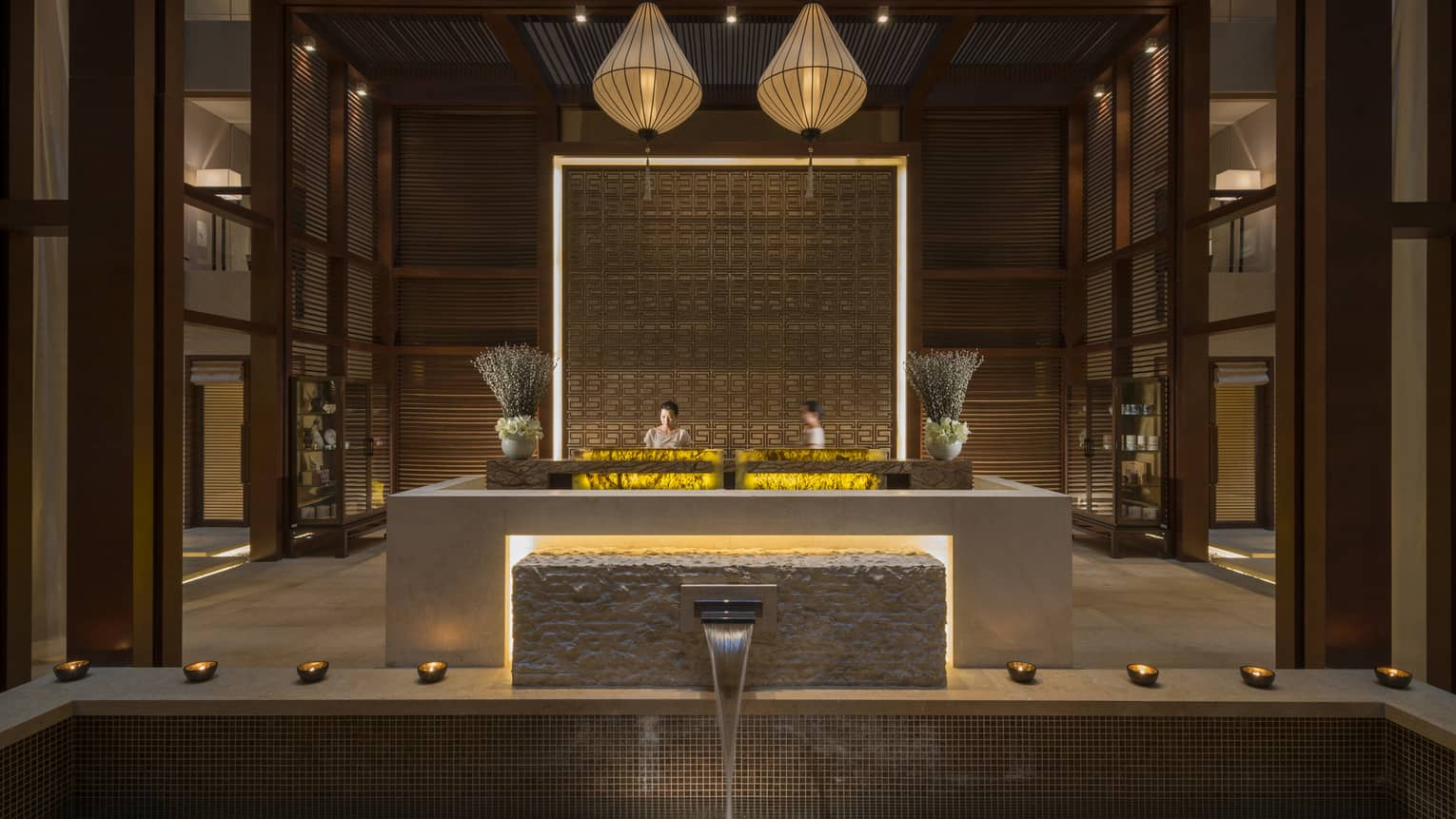 Water pours from fountain into tile pool in front of hotel spa lobby desk