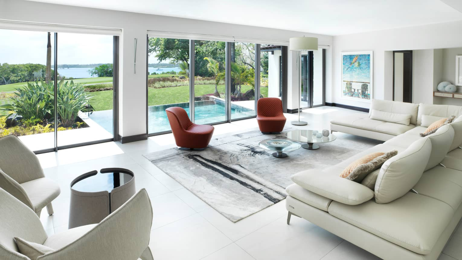 Bright, modern living room with L-shaped white leather sofa, red chairs, wall of sunny windows