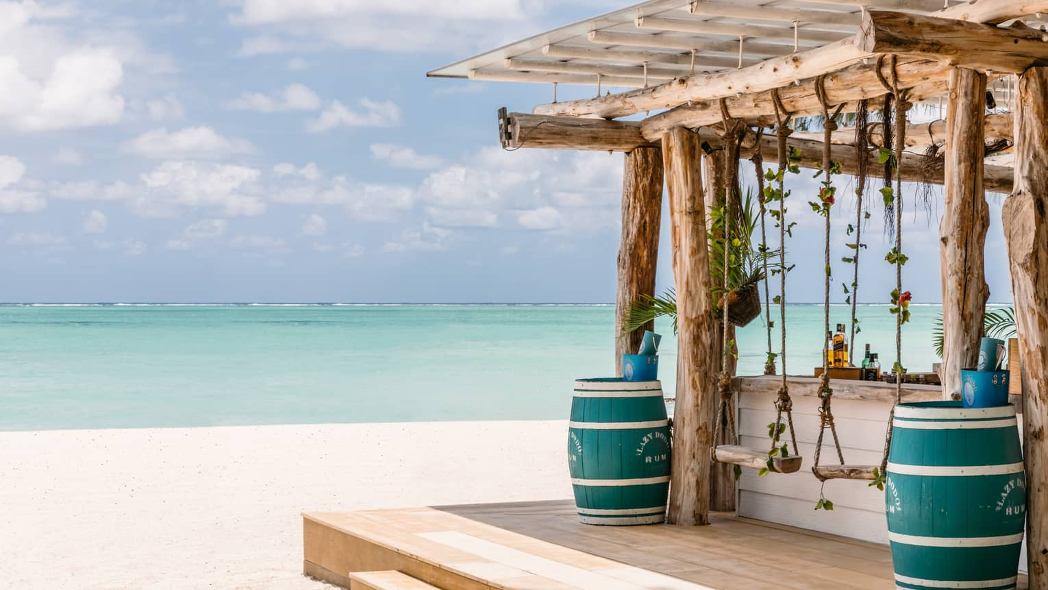 Wooden bar with pergola, two blue barrels, two swings on beach, aqua views, cloud dotted blue sky