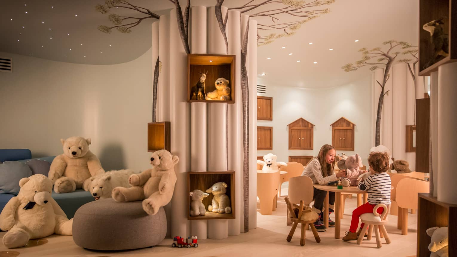 Kids play with toys at small table near chairs, stuffed bears in Kid Kingdom playroom