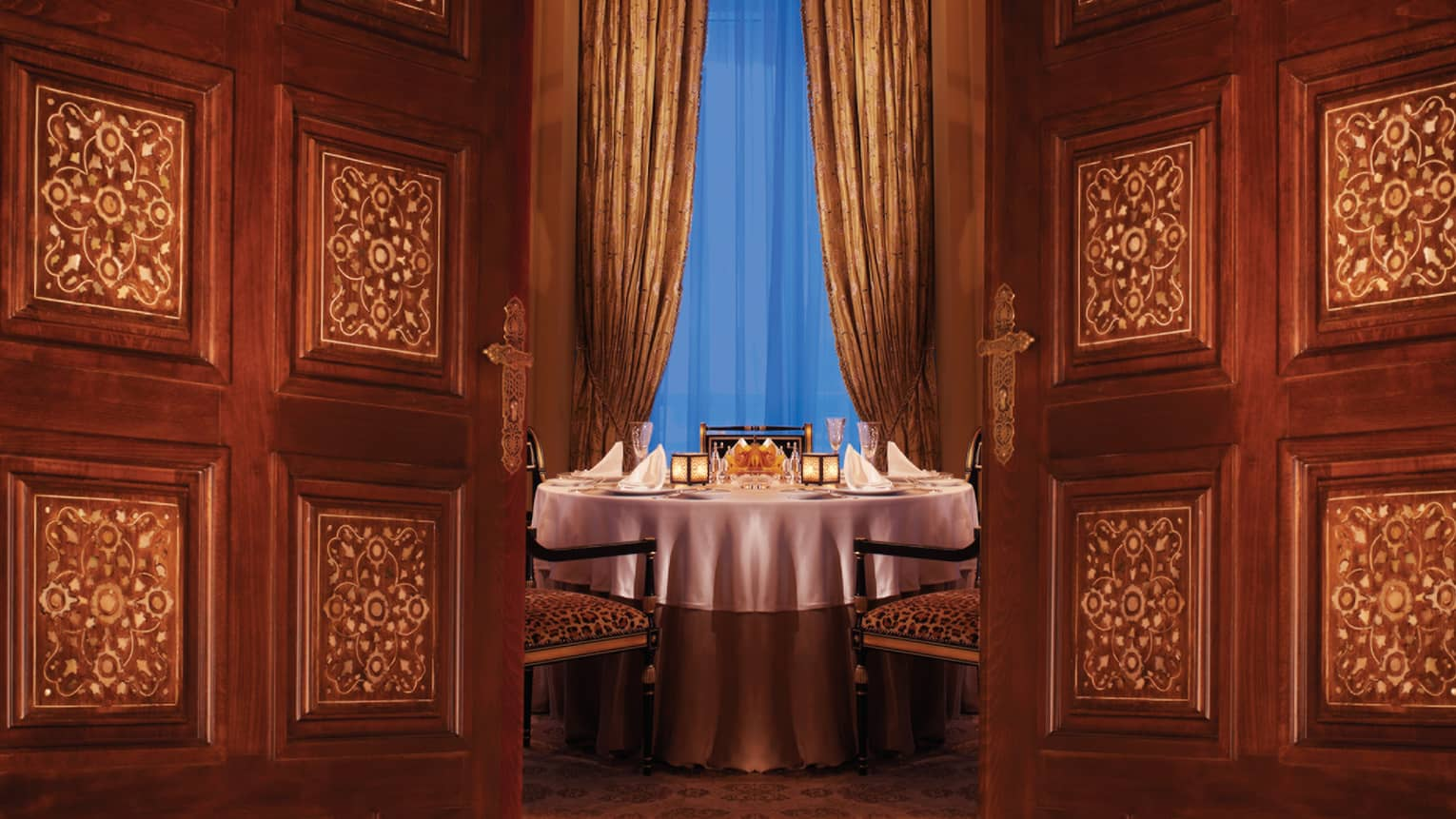 Byblos Restaurant round candle-lit dining table visible between two decorative wood doors