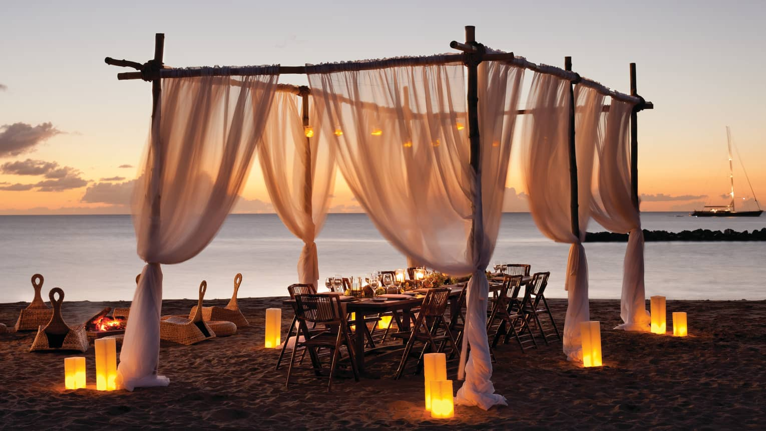 Private dining table under canopy on candle-lit beach at sunset