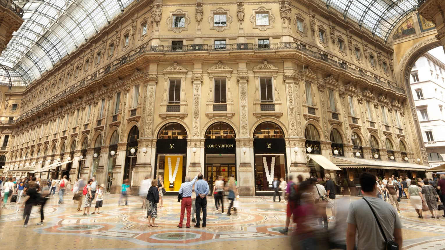 Shoppers gathered in  historic Galleria Vittorio Emanuele building with soaring ceilings, shops