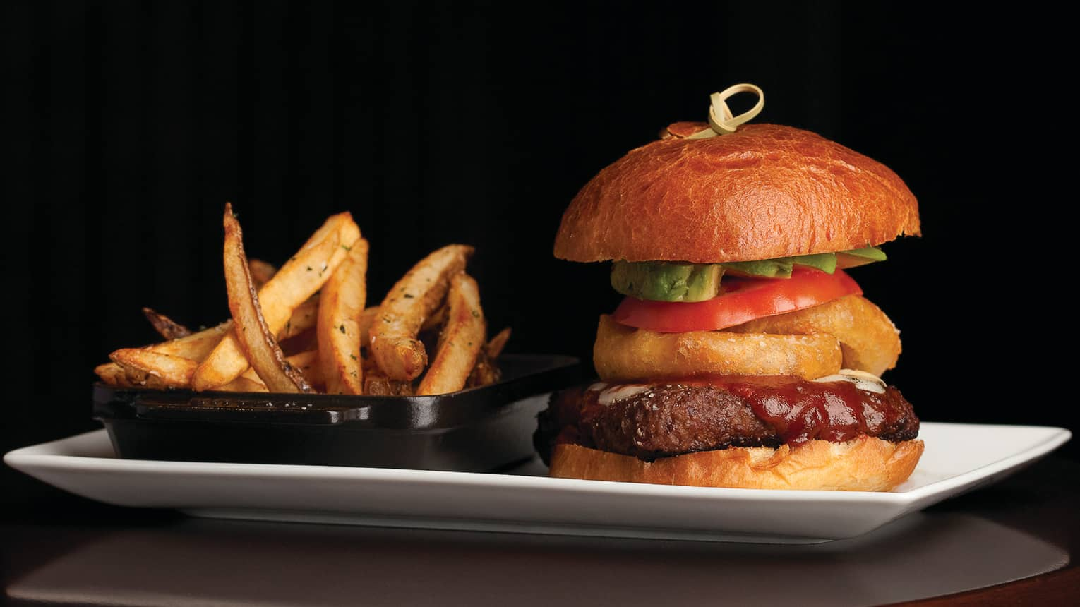 Thick bison burger with onion rings, tomato, lettuce on bun, basket of fries