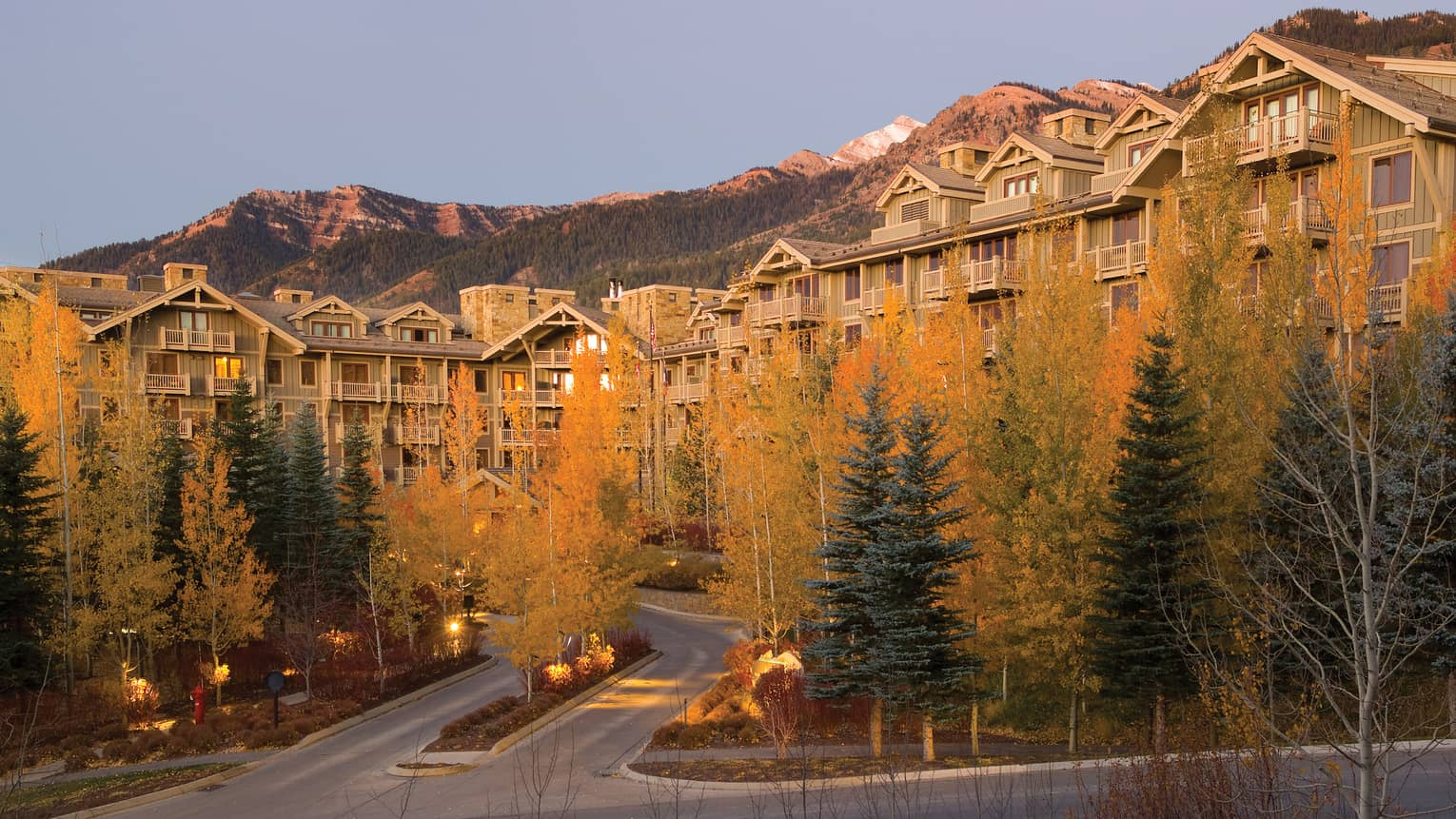 Colourful autumn trees in front of Four Seasons Resort Jackson Hole exterior with mountains in the background