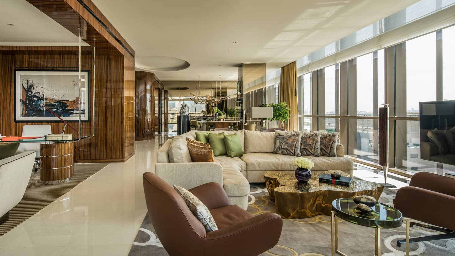 Penthouse Suite with large L-shaped beige sofa with pillows, leather armchairs, floor-to-ceiling windows along wall