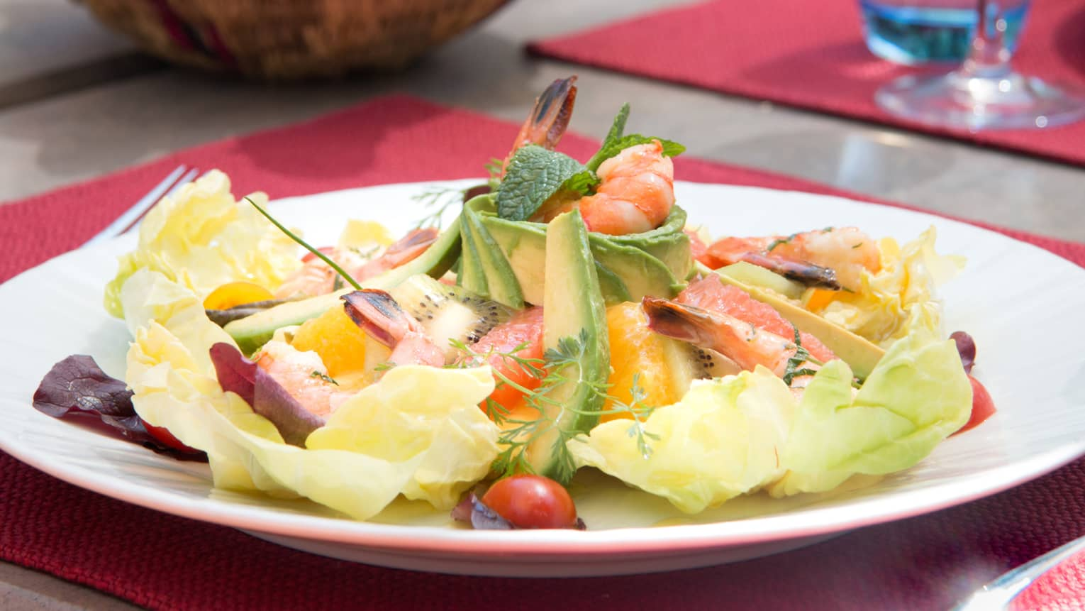 Cobb gambas salad with sliced avocado, egg, fruit arranged in layers on plate