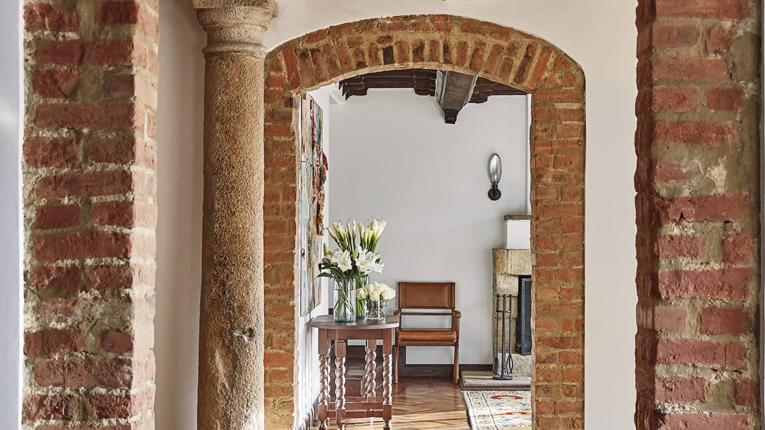 Rustic brick archways, pillars, lead to bright hotel room with wood table with fresh white flowers