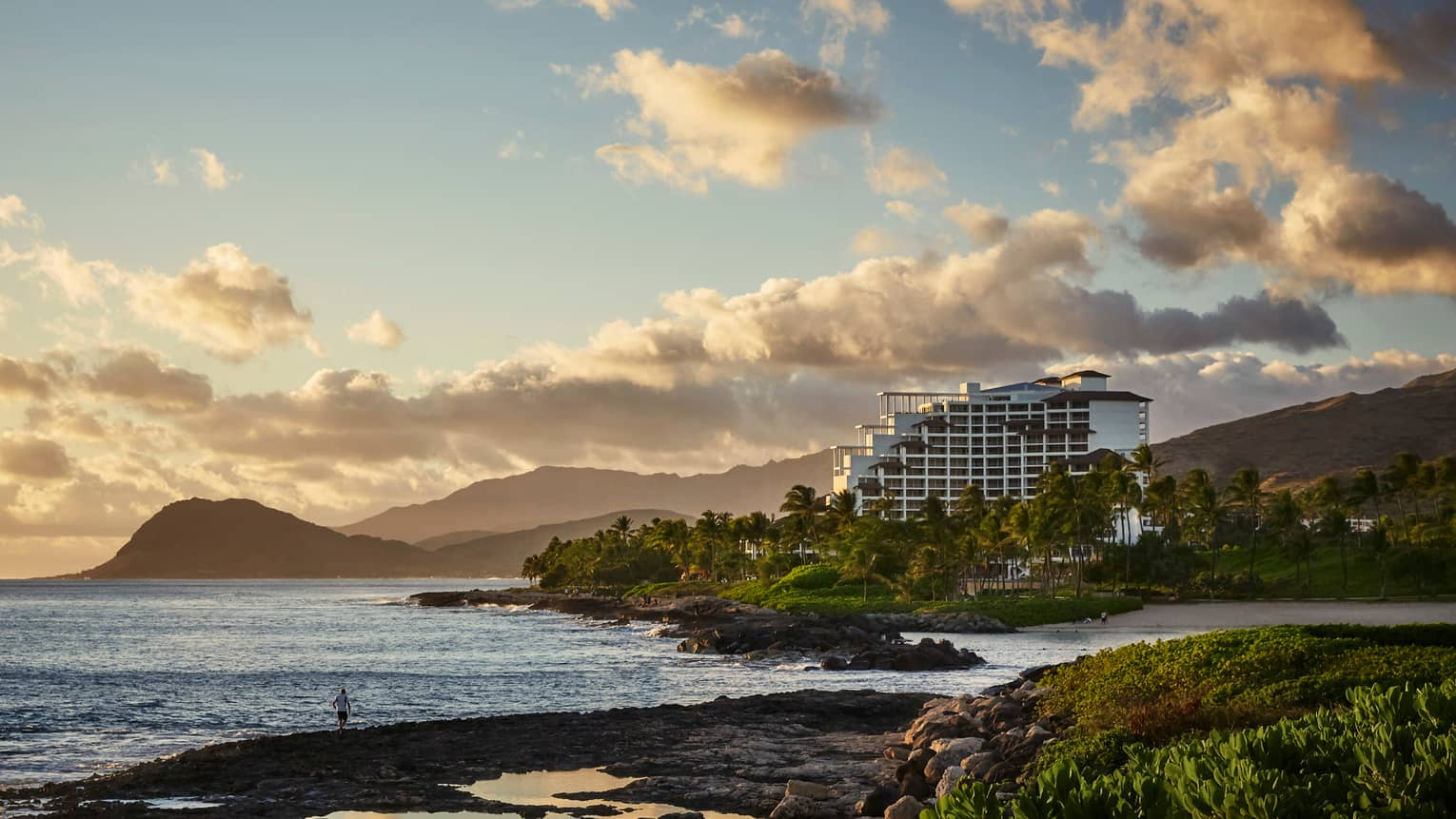 Sunset over Four Seasons Resort Oahu building on rugged coast, Waianae mountains