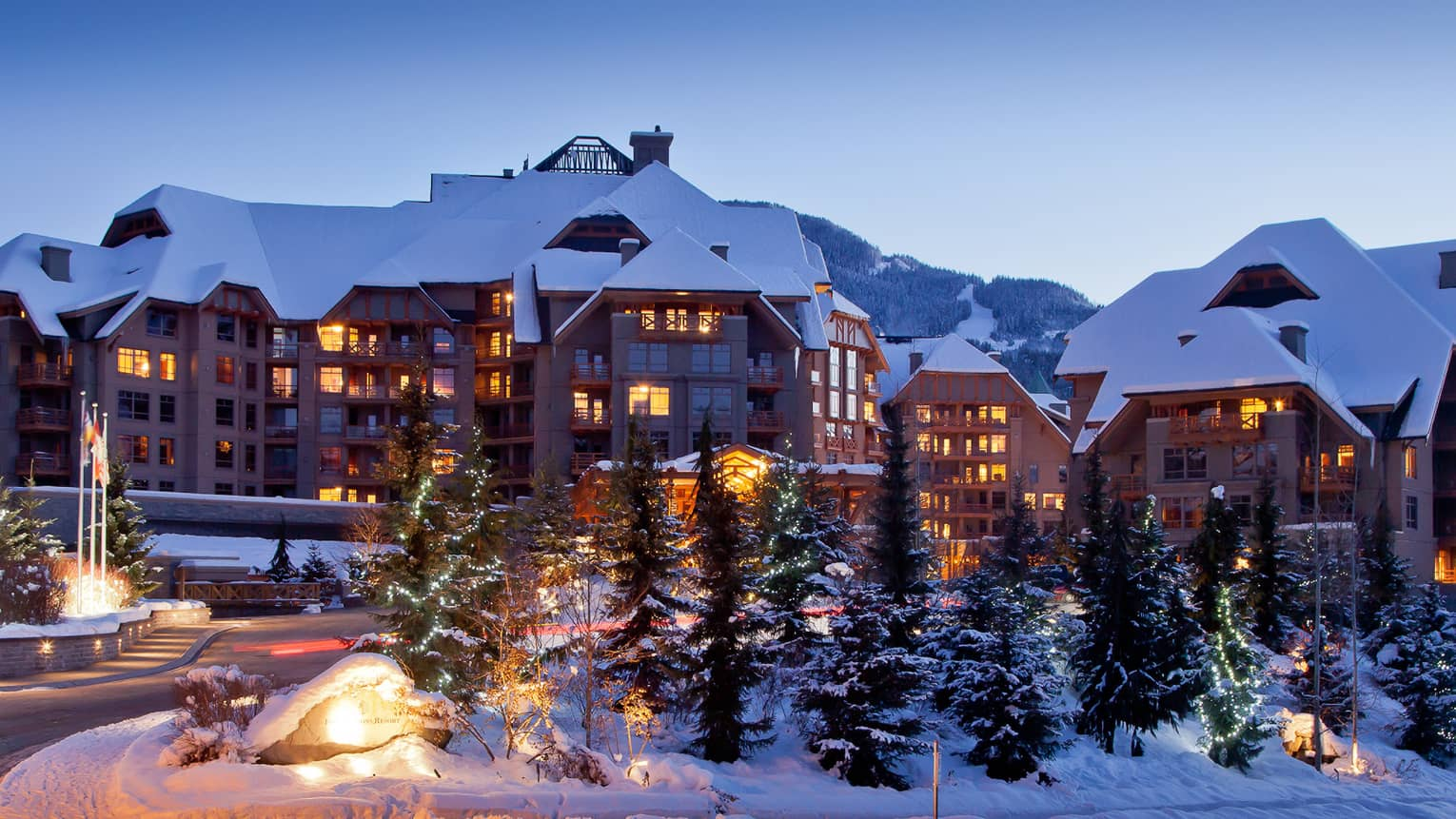 Snowy Four Seasons Hotel Whistler ski lodge at dusk with illuminated windows, snow-covered trees