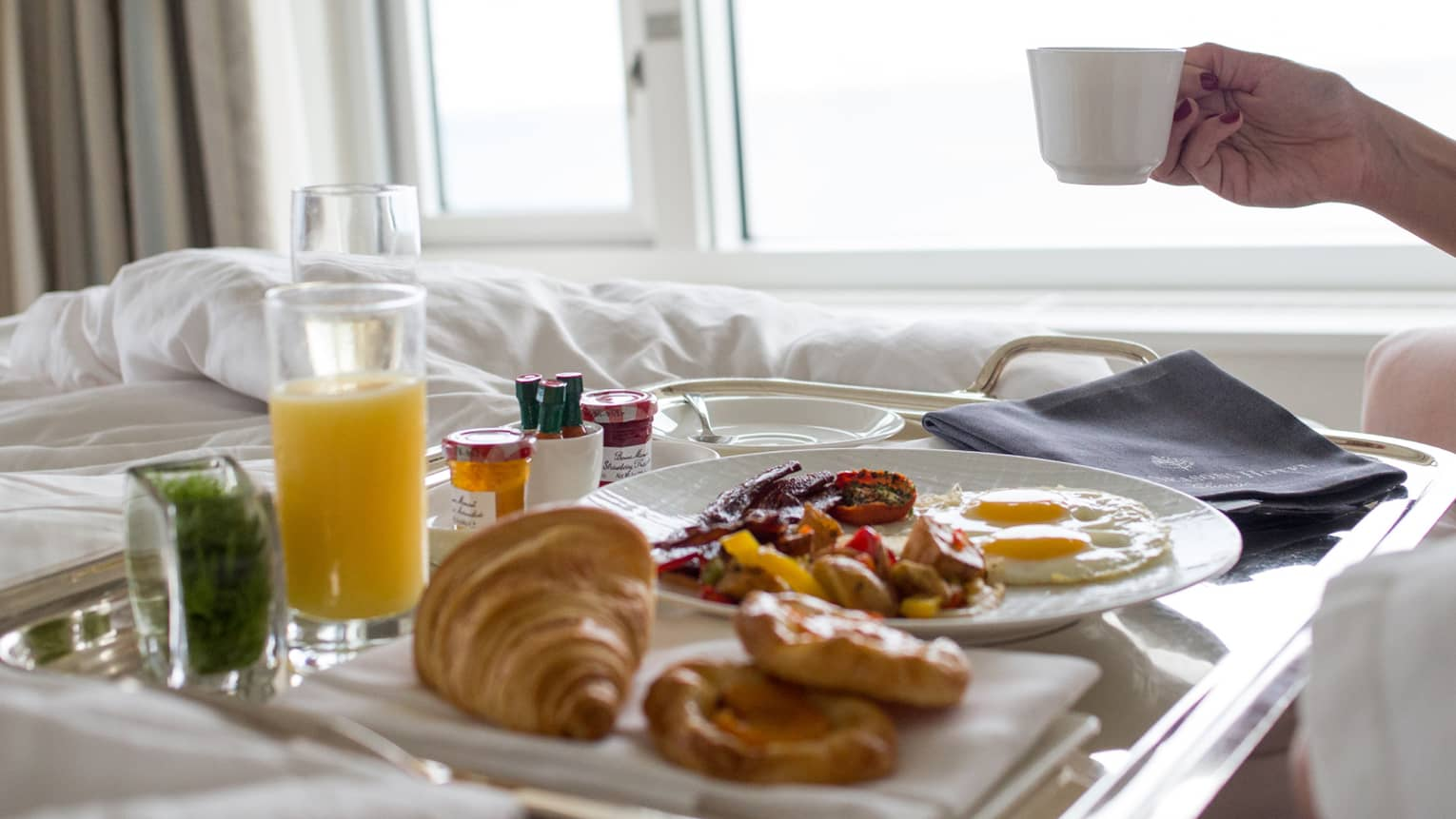 Woman holds coffee mug over in-room dining breakfast tray half with pastries, two fried eggs, roast potatoes, small jam jars