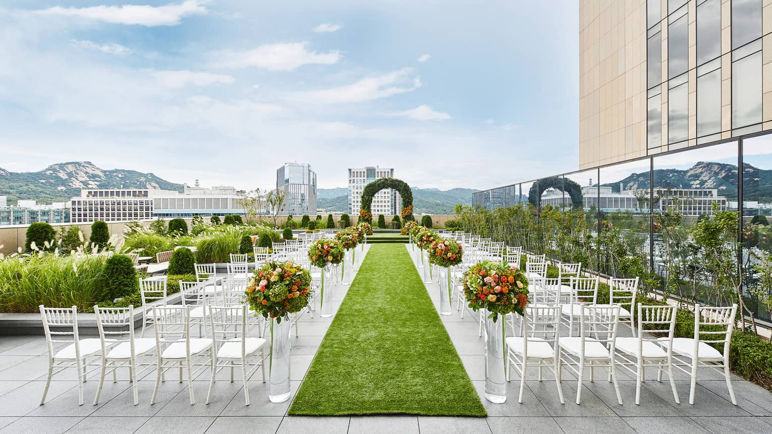 Rooftop patio wedding ceremony set up, rows of white chairs and green aisle facing altar