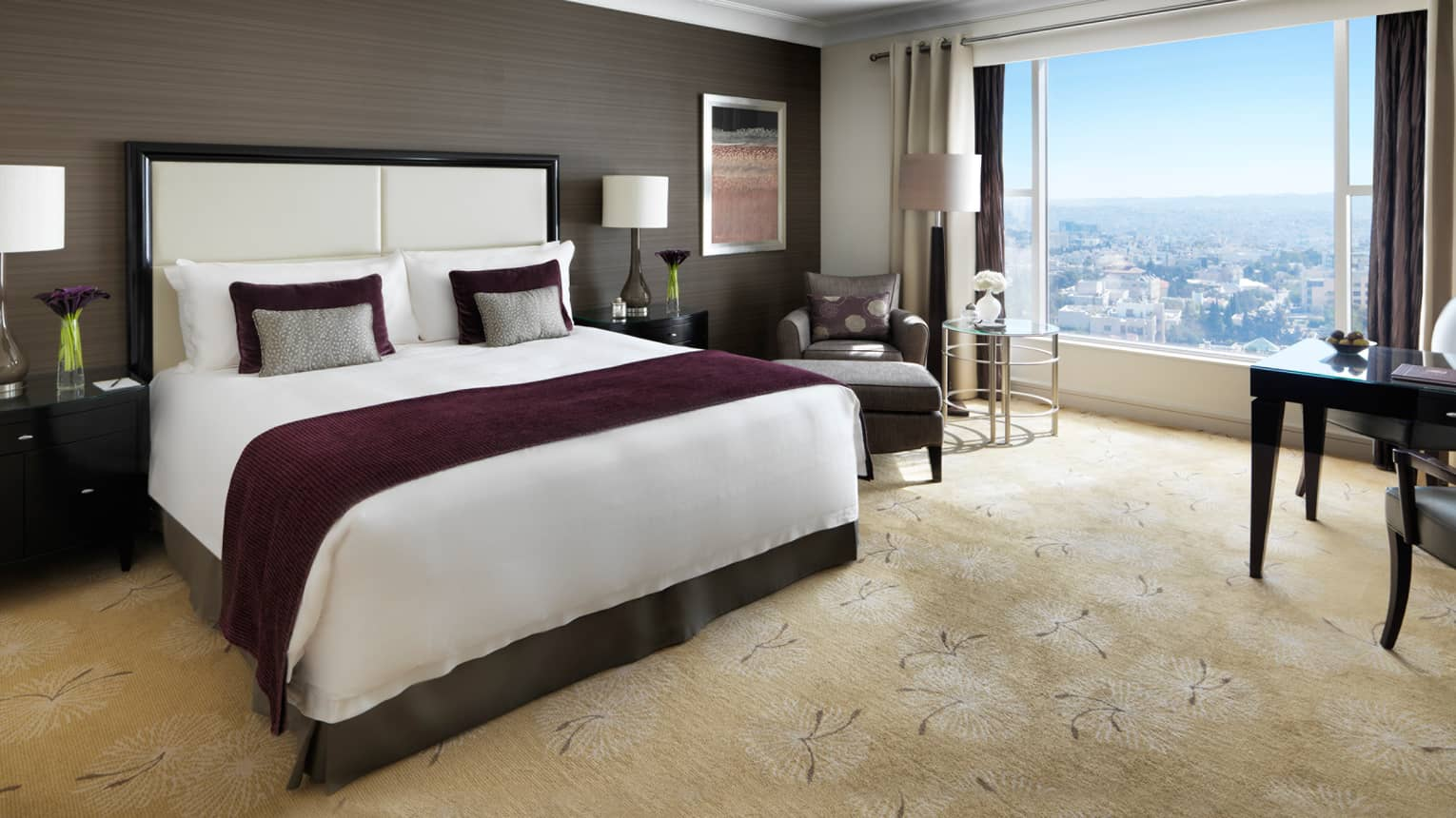 Premium room bed with burgundy blanket, wood-grain wall, plush carpet, window overlooking Abdoun area