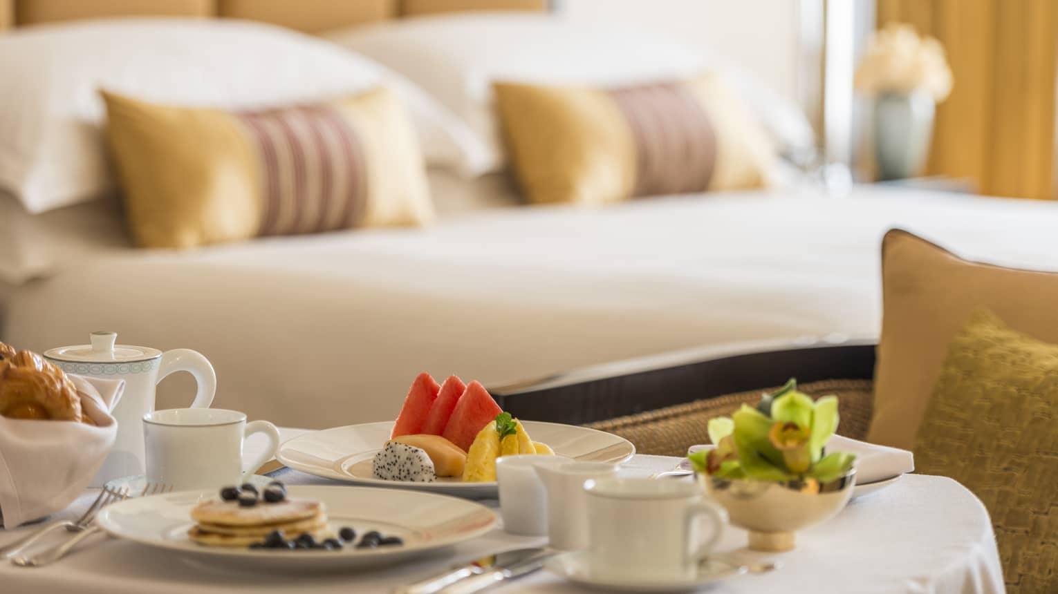 Pancakes, coffee, fresh fruit breakfast items on in-room dining table in front of bed