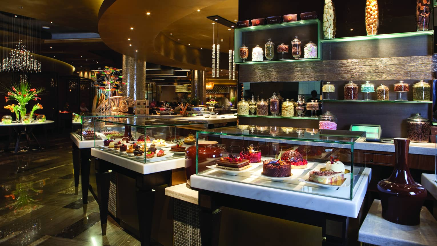 A restaurant featuring a buffet counter with displayed desserts and food