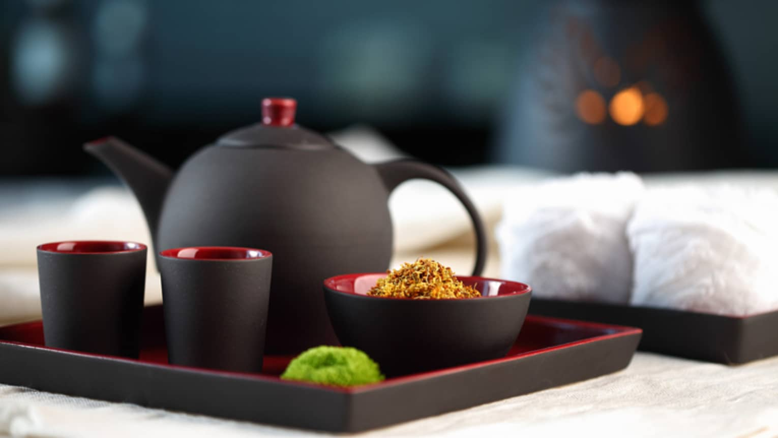 Black-and-red modern teapot with two mugs and bowl of loose-leaf chamomile on serving tray