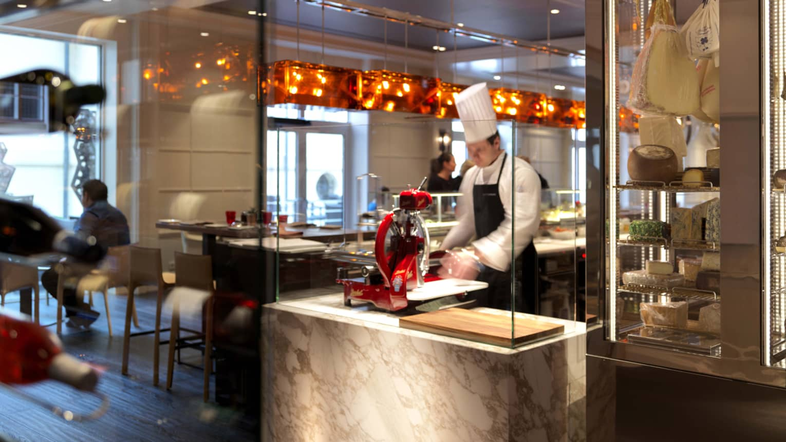Chef in tall white hat, apron slices food with machine at CottoCrudo cooking station