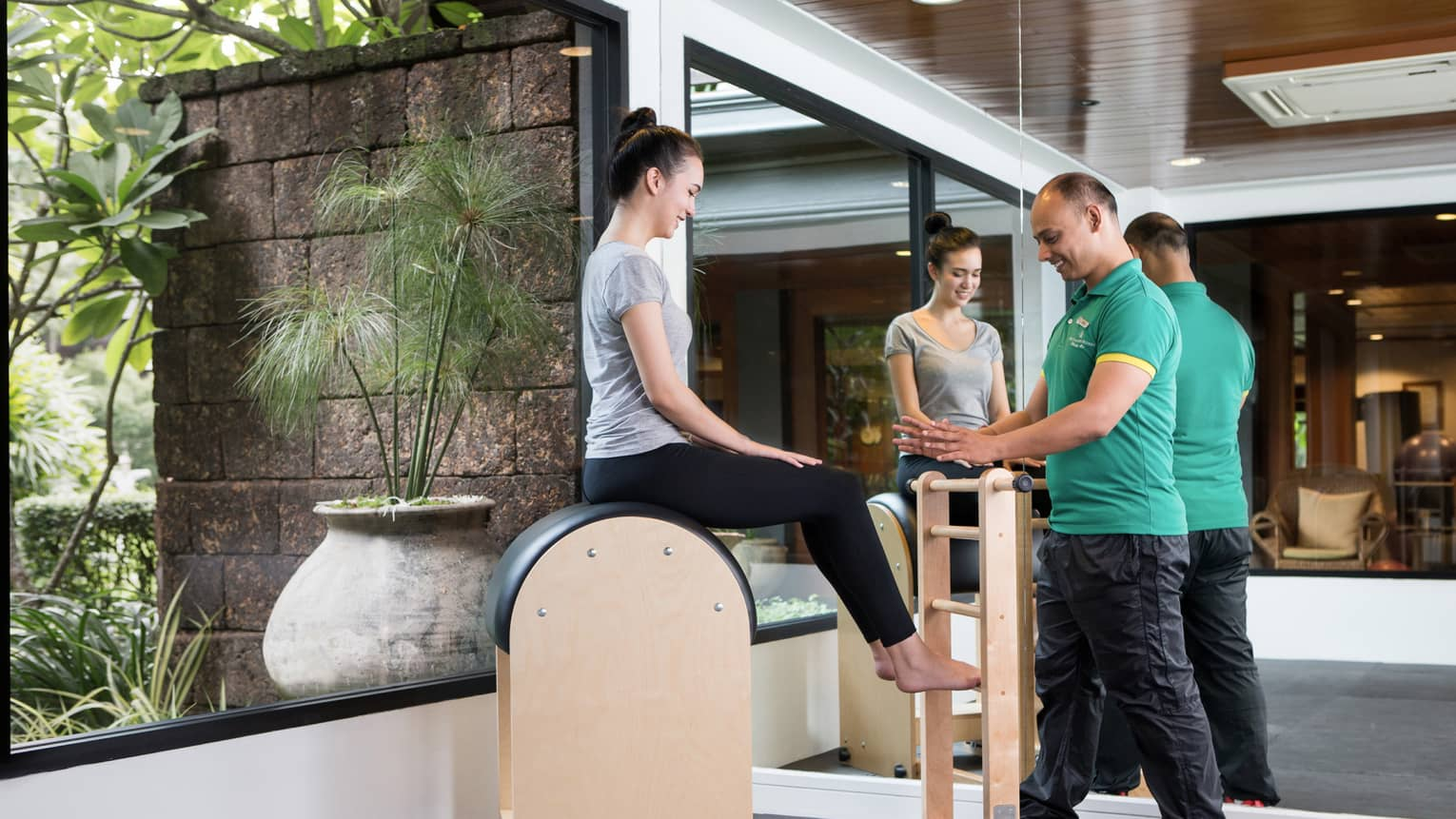 Four Seasons trainer assists woman balancing on pilates beam in Fitness Centre
