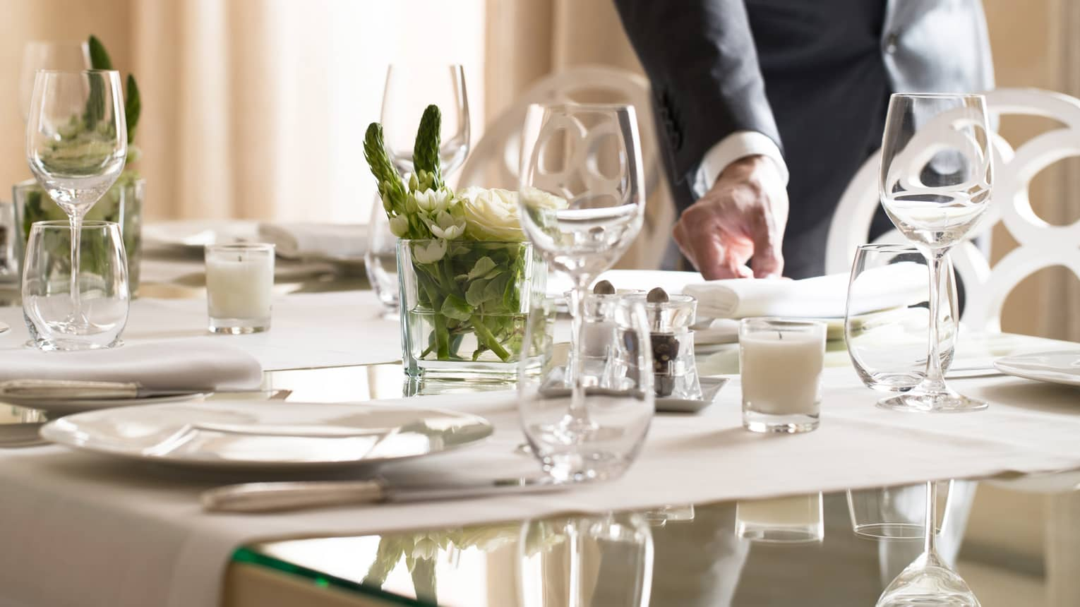 Hotel staff places napkin on small, elegant dining table in sunny room