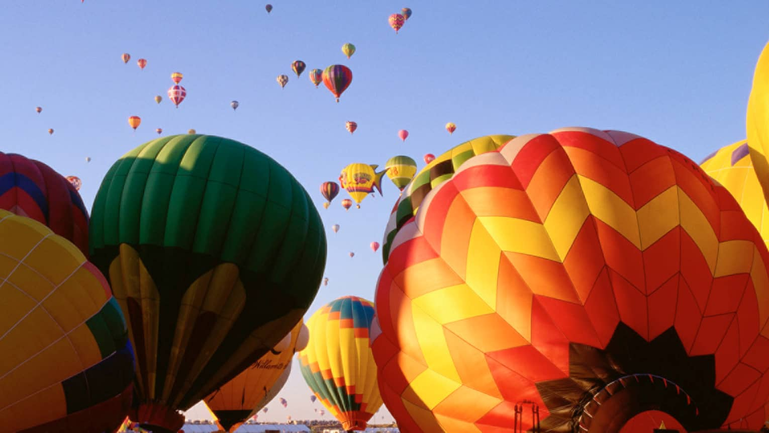 Clusters of colourful hot air balloons rising into blue sky