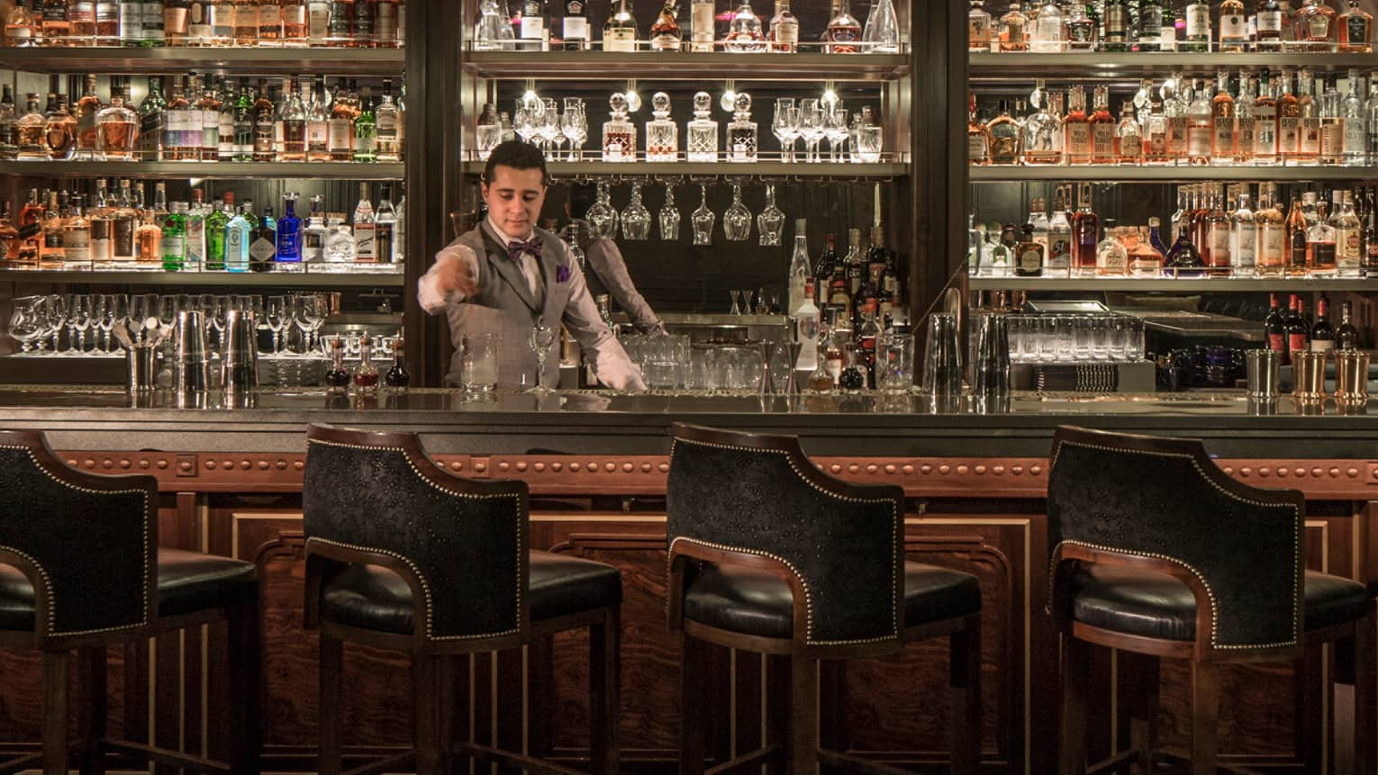 SIRR bartender in vest stands behind bar stirring cocktail, glasses and bottles lining wall behind him
