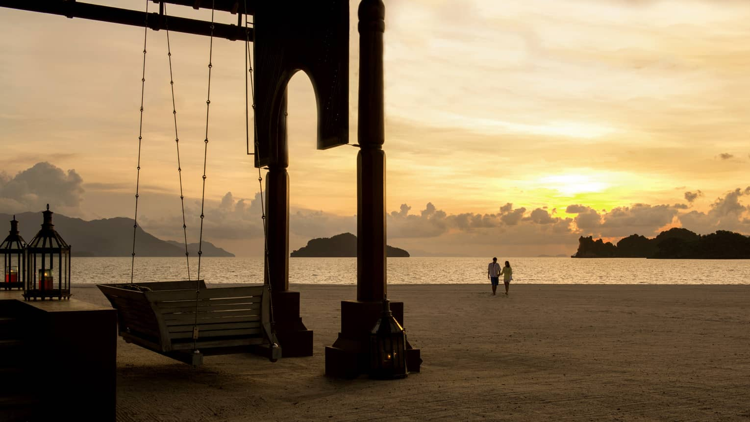 Silhouettes of couple walking along beach past wood swing, pavillion at sunset