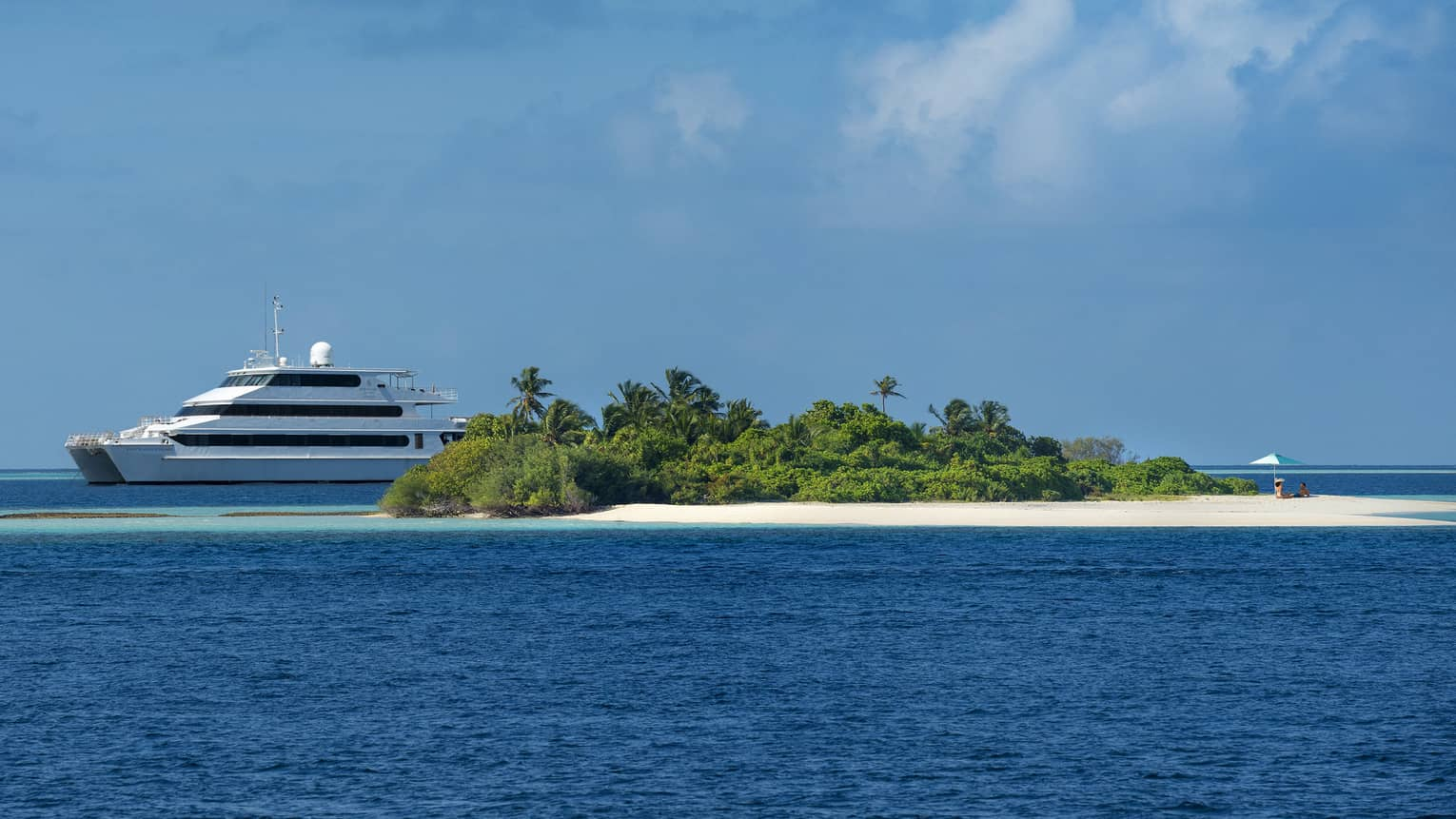 Island Explorer three-storey catamaran sailing behind small private island with white sand, trees