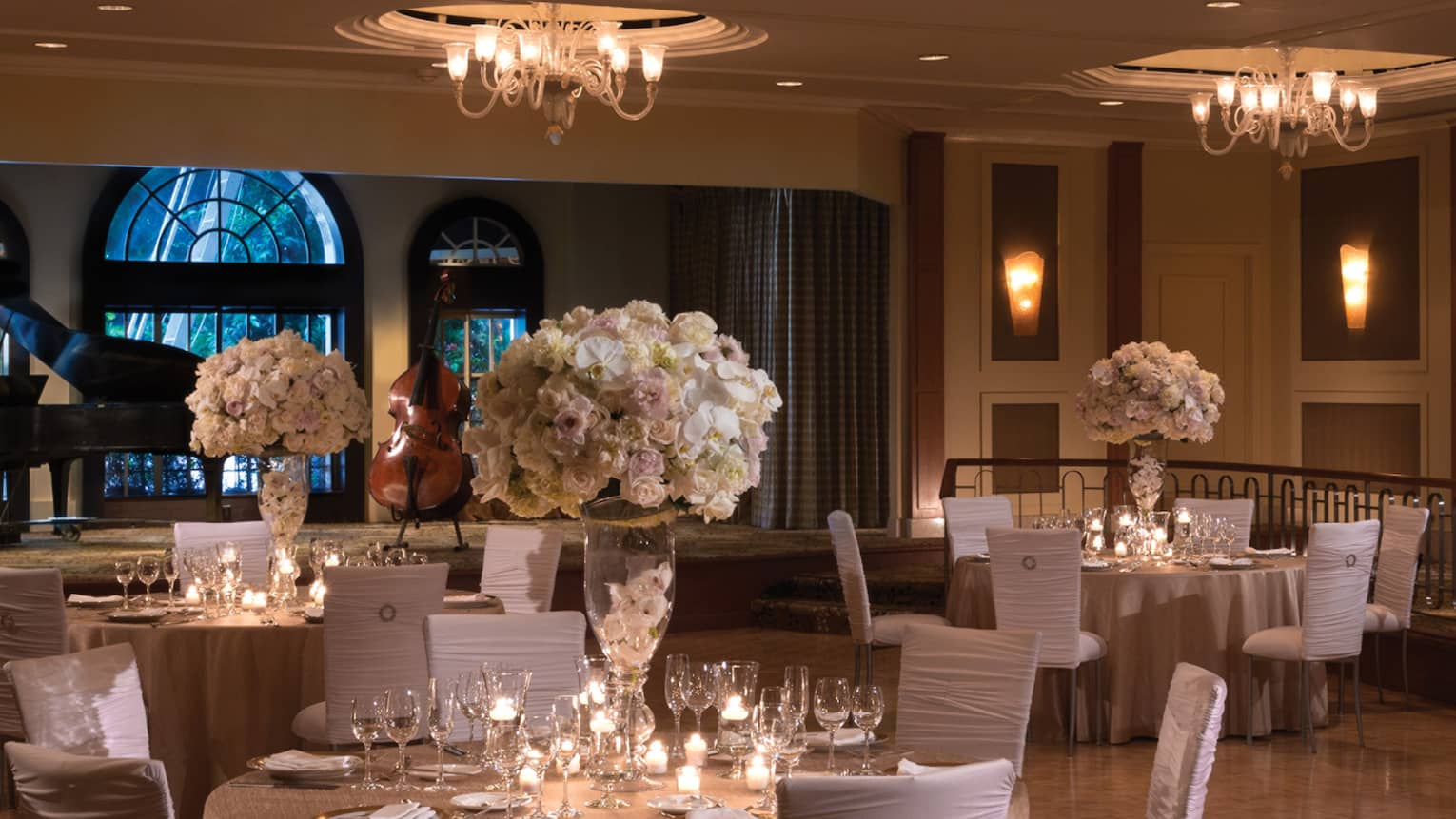 Elegant wedding reception tables with white chairs, flowers on ballroom floor