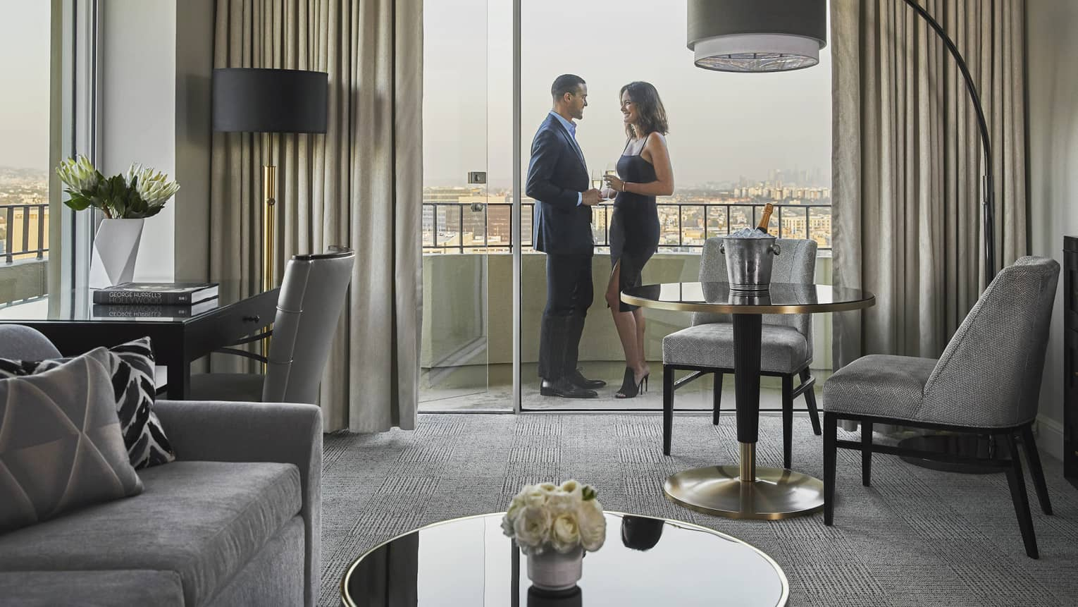 Couple wearing formal attire stand on hotel suite patio off seating area