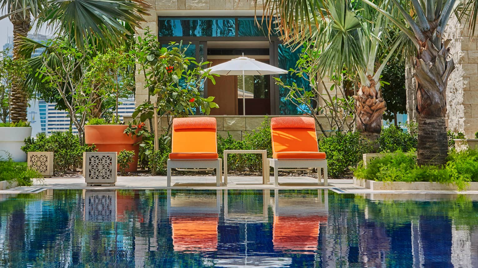Two orange patio chairs in front of palm trees, tropical garden, swimming pool