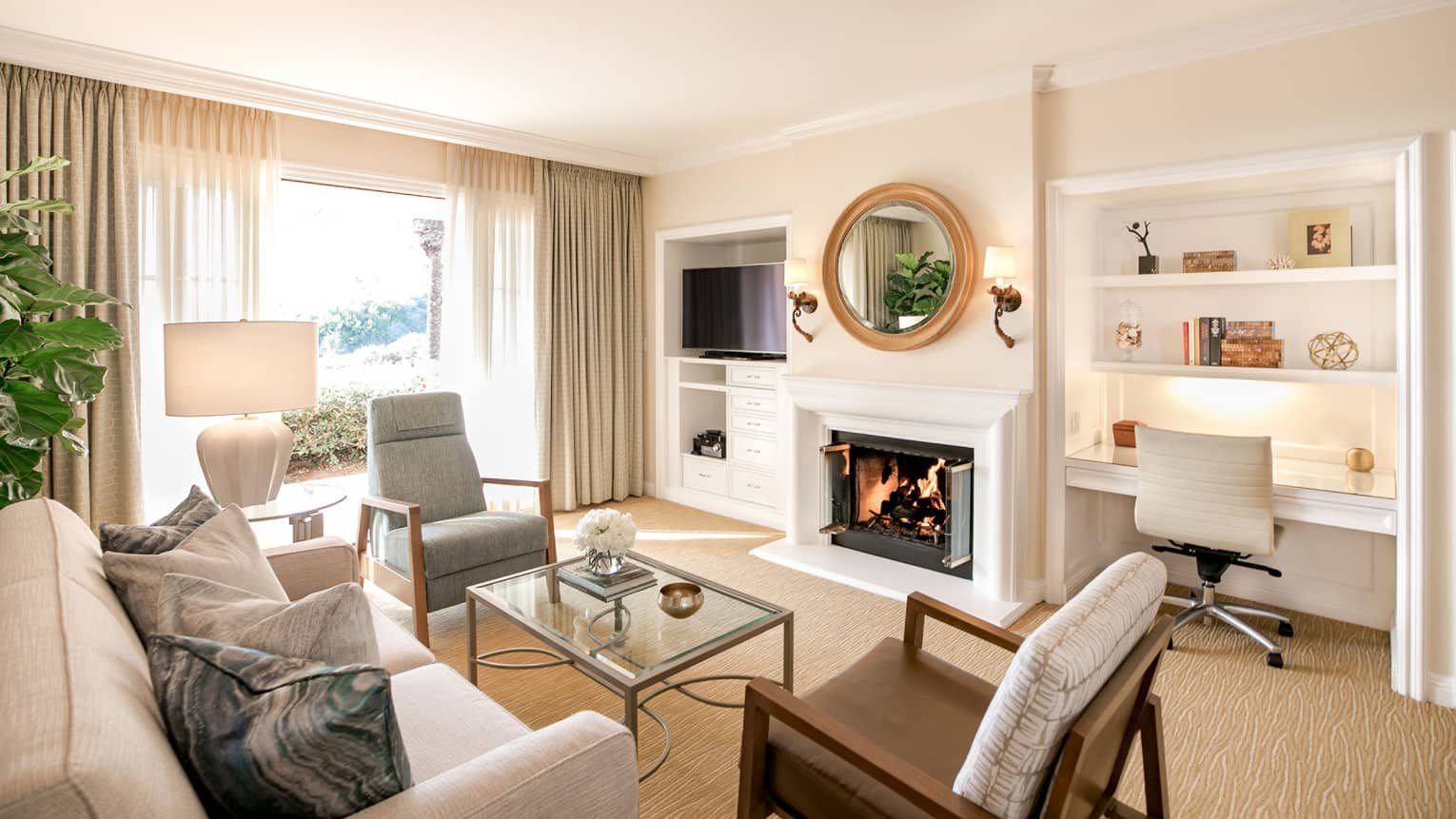 Sunny, modern villa seating room with white fireplace under round mirror, by built-in desk