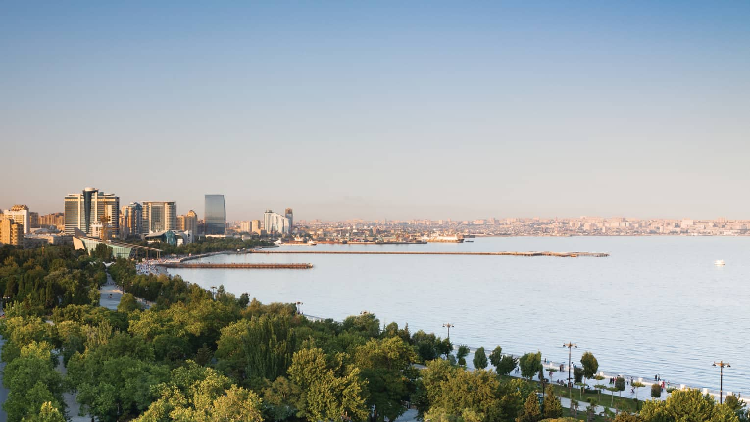 Aerial view of Baku skyline during the day with canopy of trees, high rise buildings, Caspian Sea