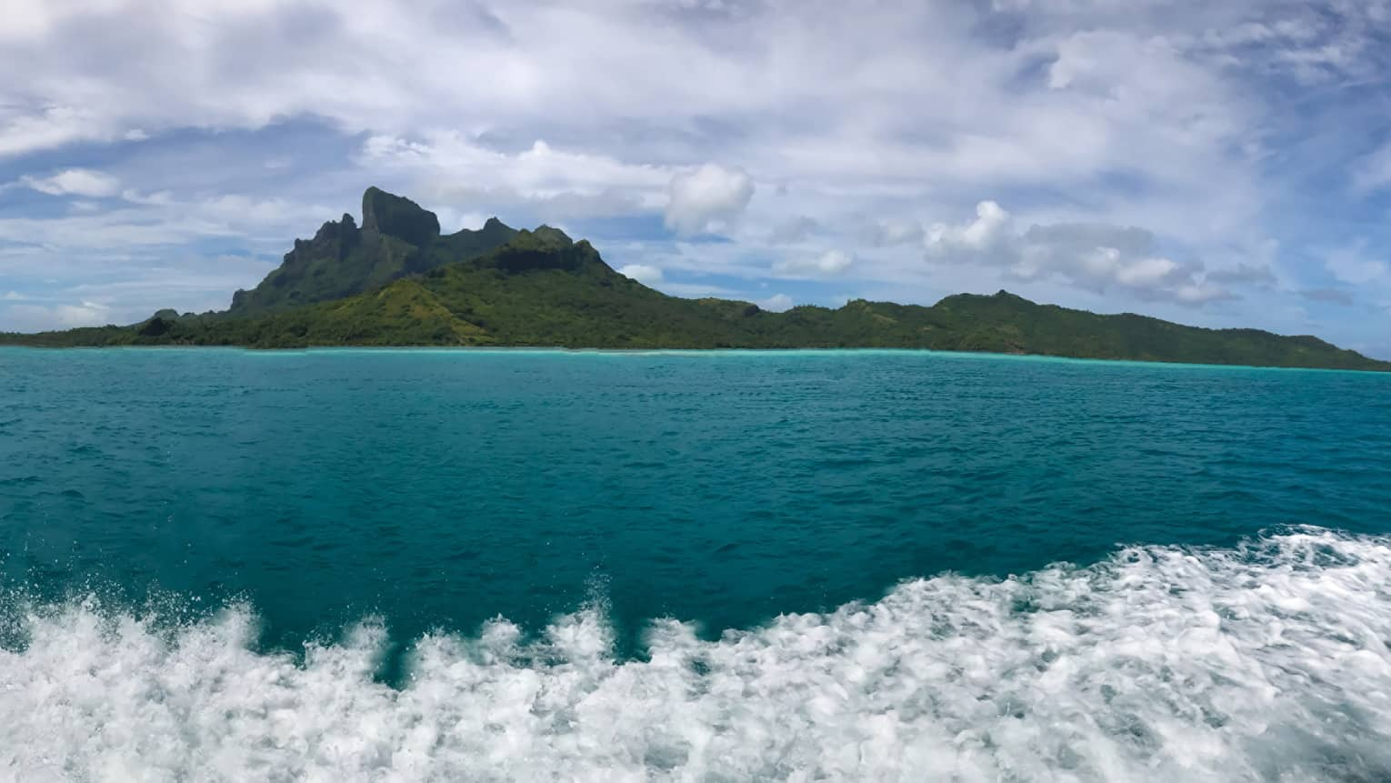 View of deep turquoise water in Bora Bora, with mountains in the distance
